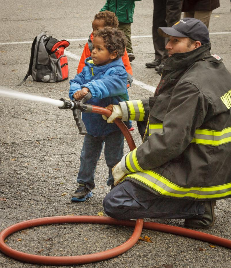 truck and tractor day kid using fire hose