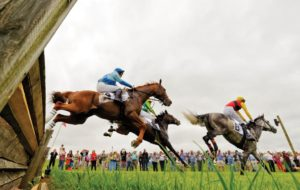 3 horses jumping a fence